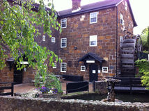 Old stone walled hotel with water wheel Stock Photo