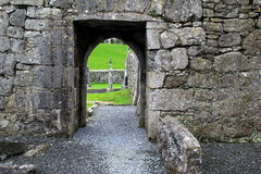 Old stone walls and archways leading to gravestones in old cemetery Royalty Free Stock Image