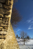 Old stone walls and snow-covered field Royalty Free Stock Photos