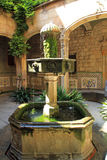 Old stone water fountain in church courtyard in Barcelona, Spain Stock Photos