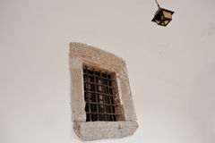Old stone window with metal grating and chandelier Royalty Free Stock Photos