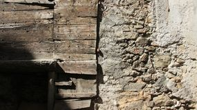 Old Wooden And Stone Walls. Old stone and wooden walls with warm sunlight in historic old town. Tirano Italy stock photos