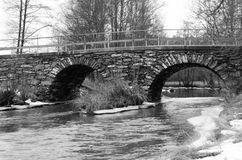 Old stonebridge over the cold water in sweden royalty free stock image