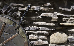 The old stonework with a wheel on cart Stock Image
