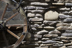 The old stonework with a wheel on cart. The old stonework with a wheel on a cart. Grunge background Royalty Free Stock Photos