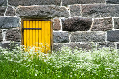 Old stony barn with yellow door Stock Image