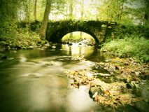 Old stony bridge above autumn river. Water of stream full of colorful leaves, leaves on gravel, blue blurred water is running over Stock Photos