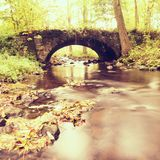 Old stony bridge above autumn river. Water of stream full of colorful leaves, leaves on gravel, blue blurred water is running over Stock Image