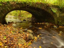 The old stony bridge above stream. Water of brook full of colorful leaves, leaves on gravel, blue blurred water is running. The old stony bridge above stream Royalty Free Stock Photography