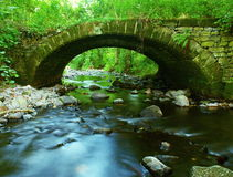 The old stony bridge of mountain stream in leaves forest, cold blurred water is running bellow. royalty free stock image