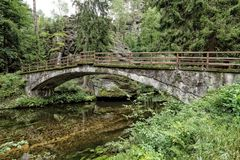 Old stony bridge over the clean river. Old stony bridge with wooden railing over the clean river Stock Photo