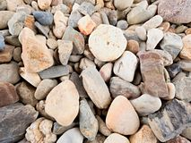 Old stony pavement from natural gravel, dry rounded and colorful pebbles. Stock Photos