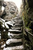 Old stony steps with rusty metal banisters to the steep rock track. Old stony steps with rusty metal banisters on right side to the steep rock track stock image