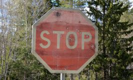 Old stop sign with bullet holes. Far into the country in nowhere Royalty Free Stock Photo
