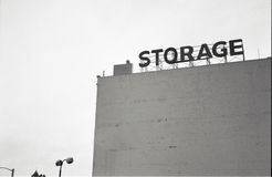 Old storage building. The large blank wall of an old warehouse with the word storage on a frame on the roof stock photography