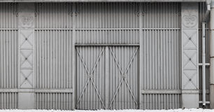 Old storage building wall made of ridged steel. Panels with gate Stock Image