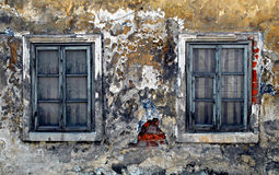 Old story. Two old ruined wooden window in the frontal of ancient home Stock Photo