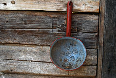 Old strainer on wooden wall. Rest rusty old strainer on a wooden wall Stock Images