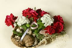 Straw basket with a bouquet of red roses, white hydrangeas and eucalyptus branches with sea shells stock images