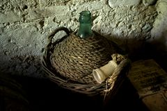 Old demijohn with mature red wine. Old straw-covered demijohn with aged red wine Royalty Free Stock Images