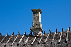 Old Straw Roof with Brick Chimney Stock Photo