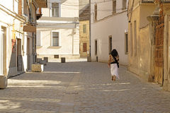 Old street. A lonely girl walking in a very old street-Cluj Napoca,Romania Royalty Free Stock Image