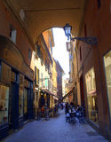Old street archway Bologna Italy. Outdoor cafe seating on a narrow street in Bologna old city,Italy Stock Image