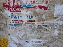 Old Street Billboard With Torn Peeled Poster Horizontal Background. Outdoor Bulletin Board Or Plywood Panel With Worn. Advertising Message, Notice And Stickers royalty free stock photography