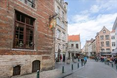 Old street with brick houses and restaurants of historical city and tourists walking around royalty free stock image