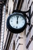 Street clock on the facade of the building Royalty Free Stock Photos