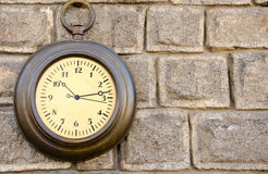 Vintage clock on a stone wall Stock Photo