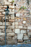 Old street lamp. An old street metal lamp in front of a stone wall Stock Image