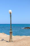 Old street lamp at the beach on Crete island Stock Photos