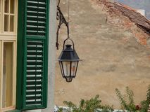 Old street lamp and a green shutter. With roofs of medieval houses in the background. Sighisoara, Romania royalty free stock photos