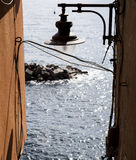Old street lamp hanging between the houses on the sea background. Italy. Stock Images