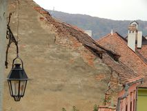 Old street lamp with roofs of medieval houses. In the background. Sighisoara, Romania royalty free stock image