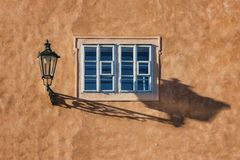 An old street lamp and shadow on a wall with a window. An old street lamp with a modern electric bulb on a wall with a window. Czech. Prague Stock Photos