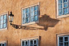 An old street lamp and shadow on a wall with a window. An old street lamp with a modern electric bulb on a wall with a window. Czech. Prague Royalty Free Stock Image