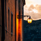 Old street lamp at sunset in Malcesine, on Lake Garda, Italy. The Dolomites mountains in the background Stock Photos