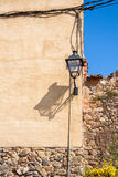 Old street lamp in the village of Pubol. The shadow of the lamp. The medieval wall of the building. Stone wall Royalty Free Stock Photos