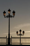 Old Street Lamps and Railings on a Bridge, Backlit by the Dawnin. Old street lamps and railings on a bridge in Chiclana de La Frontera, Andalusia, Spain. The Stock Photos