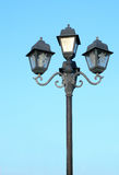 Old street light against blue sky Stock Photo