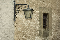 Old street light at a wall with window Stock Image