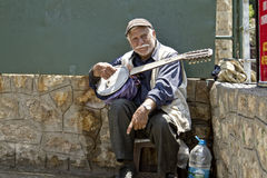 Old street musician with a guitar in hand asking for money from tourists. ANTALYA, TURKEY - MAY 14: Old street musician with a guitar in hand asking for money Royalty Free Stock Photo