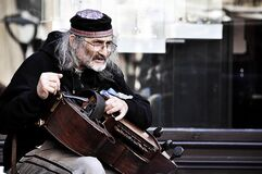 An old street musician playing the hurdy gurdy