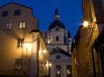 Old street in Stockholm. Small old street in Stockholm by night. Kristina church in the background Royalty Free Stock Images