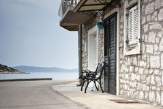 Old street of stone houses with bench by the sea Royalty Free Stock Image