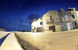 Old street of stone houses by the sea at night Stock Photo