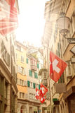 Old street with swiss flags, sunrays Stock Photo