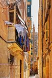 Old street with traditional houses and balconies in Valletta. Old street with traditional houses and balconies in the city center of Valletta, Malta Royalty Free Stock Photo